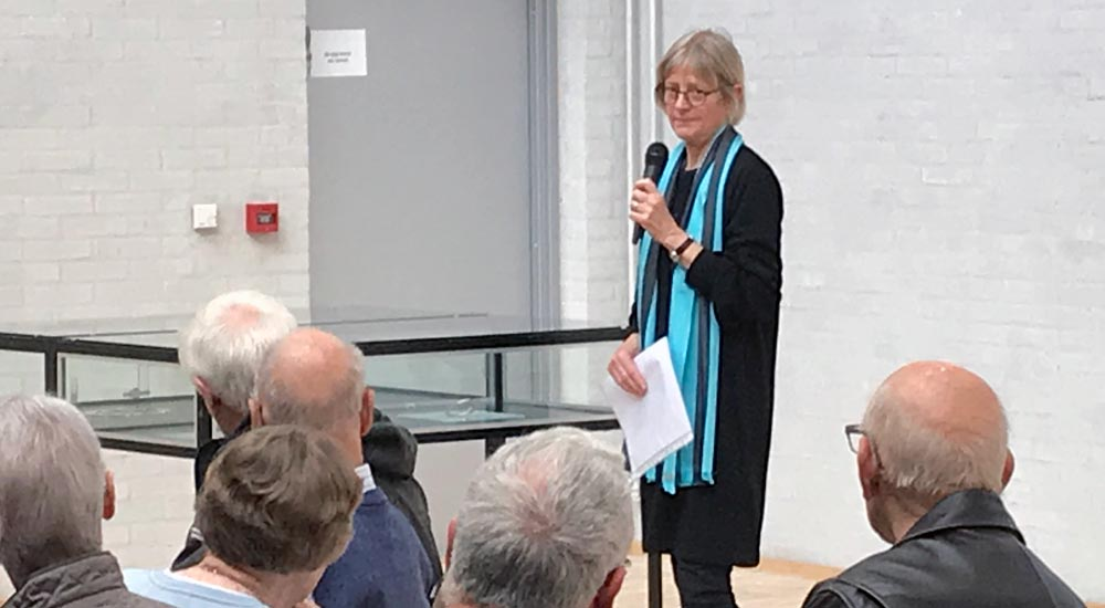 Kvinde taler i mikrofon til publikum